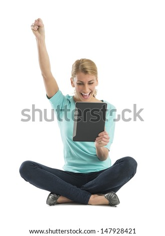 Excited young Caucasian woman with hand raised using digital tablet while sitting against white background - stock photo