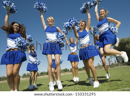 Excited young cheerleaders with pompoms cheering on field - stock photo
