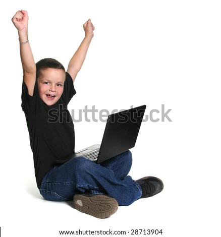 Excited Young Child Working on Computer With Arms Up in Excitement - stock photo