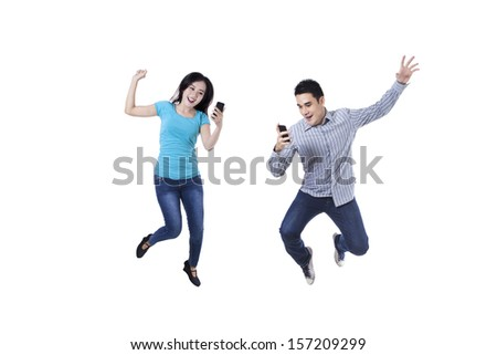 Excited young couple jumping with mobile phone - stock photo