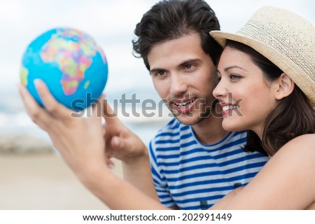Excited young couple planning their holiday holding up a globe and pointing to a travel destination with focus to the attractive woman in a trendy straw hat - stock photo