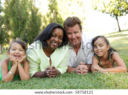 Excited young family lying down on the grass - stock photo