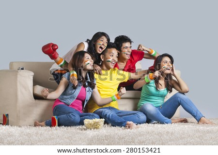 Excited young friends watching a boxing match together at home - stock photo