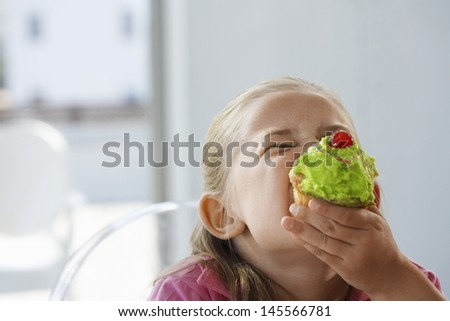 Excited young girl eating cupcake at home - stock photo