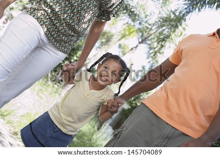 Excited young girl holding hands while walking with parents in park - stock photo