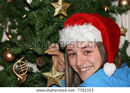 Excited young girl in a red festive hat decorating a christmas tree. - stock photo