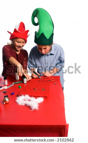 Excited young girl in an elf hat points at the nearly finished Christmas craft project of an older boy