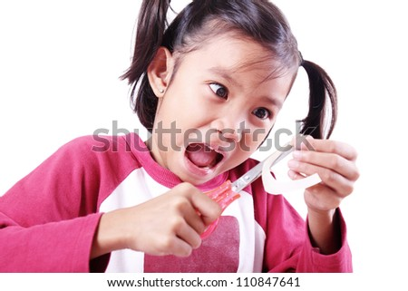 Excited young girl playing with scissor and paper. - stock photo