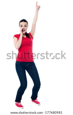 Excited young girl pointing upwards, in fun mood - stock photo