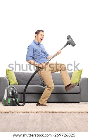 Excited young guy pretending to be playing guitar on the vacuum cleaner wand in front of a gray sofa isolated on white background - stock photo