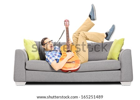 Excited young male lying on a modern sofa and playing an acoustic guitar isolated on white background - stock photo