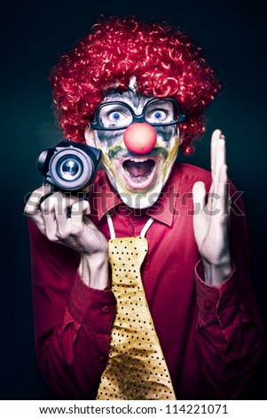 Excited Young Male Photographer Clown Holding Camera While Shouting Out Cheese At A Kids Birthday Party Celebration On Dark Studio Background - stock photo