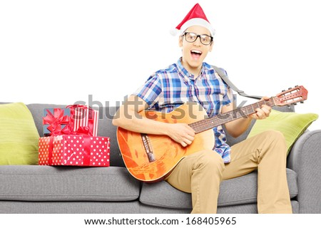 Excited young male with christmas hat seated on sofa playing an acoustic guitar isolated on white background - stock photo