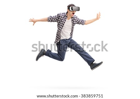 Excited young man experiencing virtual reality through a VR headset shot in mid-air isolated on white background