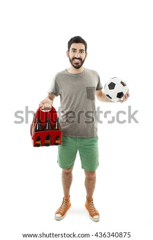 Excited young man holding ball and pack of beer. Isolated on white background