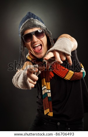 excited young man in a nice fur hat and gloves, pointing to you - stock photo