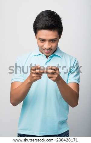 Excited young man playing game on his smartphone - stock photo