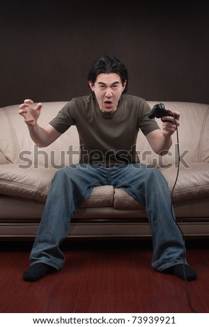 excited young man playing video games on gray background