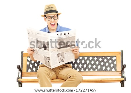 Excited young man reading a newspaper seated on bench isolated on white background