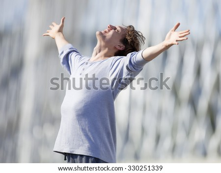 Excited Young Man Stretching out his Arm in Emotion Outdoors - stock photo