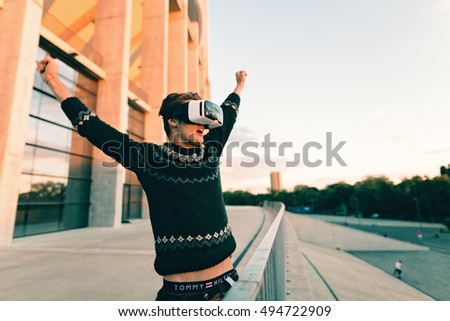 excited young man trying a pair of VR glasses show that are perfect dressed in a cool sweater and trendy outfit curious by augmented reality sunlit by an amazing sunset reflection