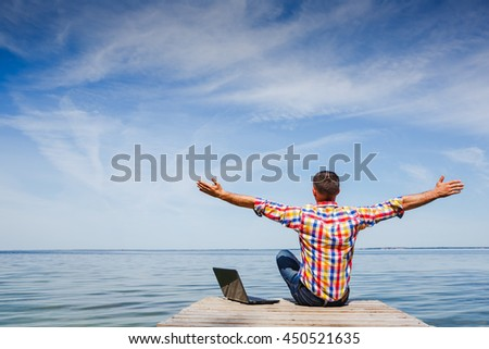 Excited young man using laptop - stock photo