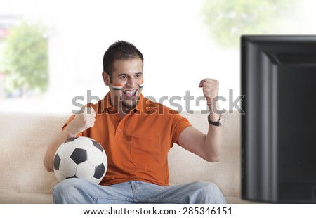 Excited young man with painted face cheering while watching soccer game on television - stock photo