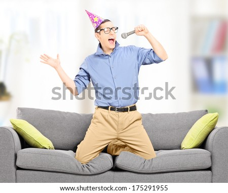 Excited young man with party hat singing on a microphone indoors, shot with tilt and shift lens - stock photo