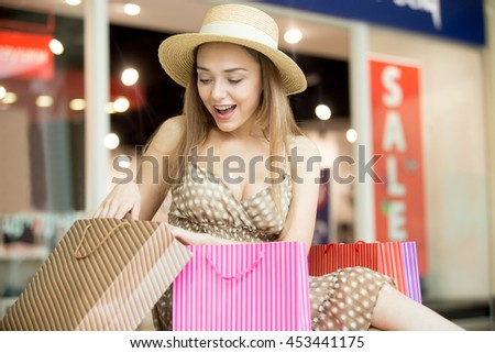 Excited young pretty woman in hat sitting in shopping centre with shopping bags. She is glad, looking at purchase with anticipation. Fashion, sale, shopping time concept. Red sale sign on background - stock photo