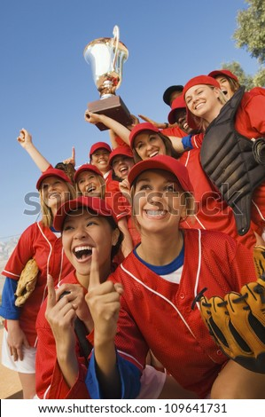 Excited young softball team cheering after a winning game - stock photo