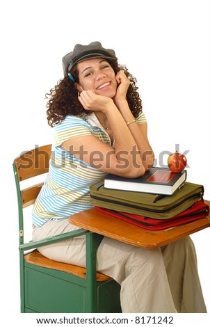Excited young student at a desk with books and an apple - stock photo