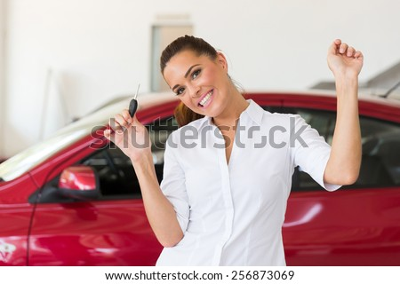 excited young woman collecting her new car from dealership - stock photo