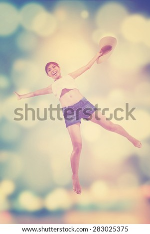 Excited young woman enjoy freedom and jumping over a light glitter background - stock photo
