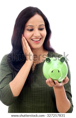 Excited young woman holding a piggy bank over a white background