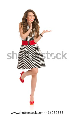 Excited young woman in black and white striped dress and high heels standing on one leg with one hand raised and the other holding on chin, Front view. Full length studio shot isolated on white. - stock photo