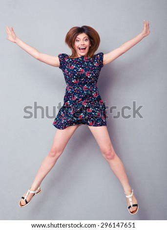 Excited young woman jumping over gray background and looking at camera - stock photo