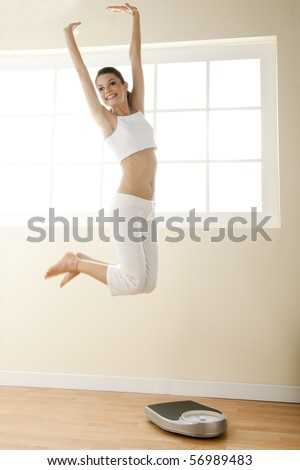 Excited young woman jumping, weight scale on the floor. - stock photo