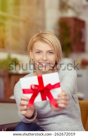 Excited young woman showing off her Valentines gift holding it in front of her with a joyful smile displaying the decorative large red ribbon - stock photo