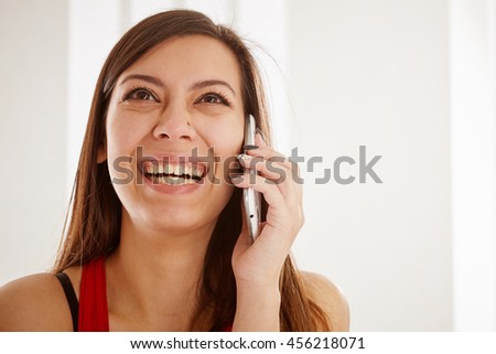 Excited young woman talking on the phone, close up.