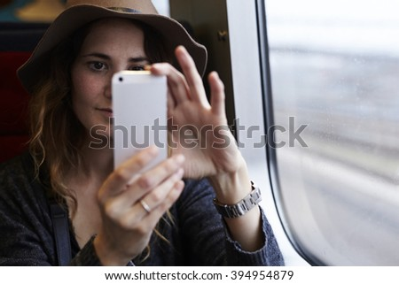 Excited young woman traveling on train, smiling - stock photo