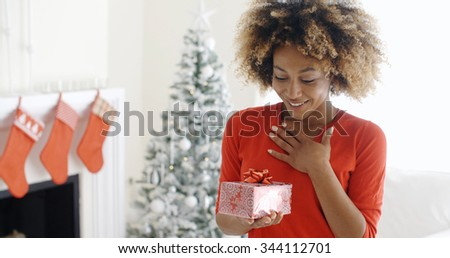 Excited young woman with an unexpected Christmas gift holding her hand to her chest with a look of surprise  decorated Christmas tree and fireplace behind - stock photo