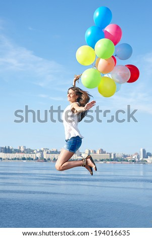Excited young woman with colorful balloons jumping over city background - stock photo
