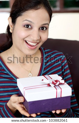 Excited young woman with gift box