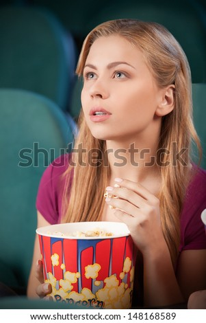 Excited young women at the cinema. Portrait of beautiful young women eating popcorn while watching movie at the cinema - stock photo