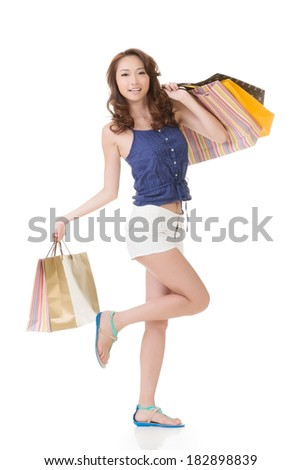 Exciting Asian shopping woman holding bags, full length portrait isolated on white. - stock photo