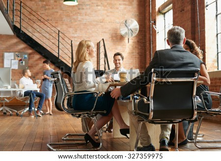 Exciting boardroom meeting with business people in trendy office space