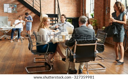 Exciting boardroom meeting with business people in trendy office space - stock photo