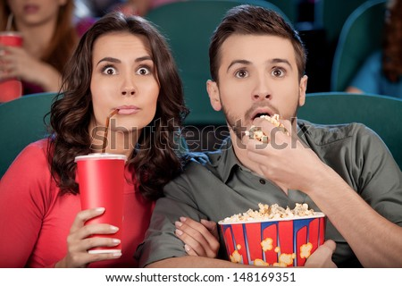 Exciting movie. Shocked young couple eating popcorn and drinking soda while watching movie at the cinema - stock photo