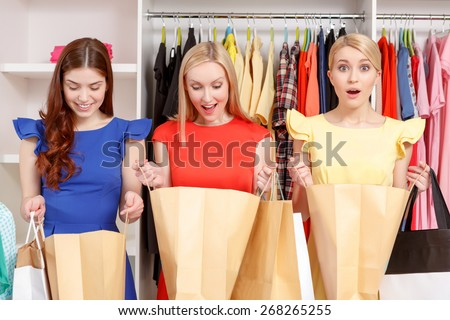 Exciting shopping. Three beautiful girl looking inside their paper bags copyspace in a store - stock photo