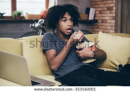 Exciting TV show. Young African man watching TV and keeping his mouth open while sitting with bucket of popcorn on the couch at home - stock photo